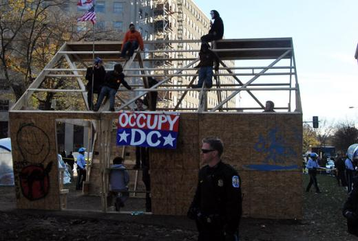 The last few Occupy DC protesters perch on the top of the structure they built over the weekend that caused a confrontation with authorities.