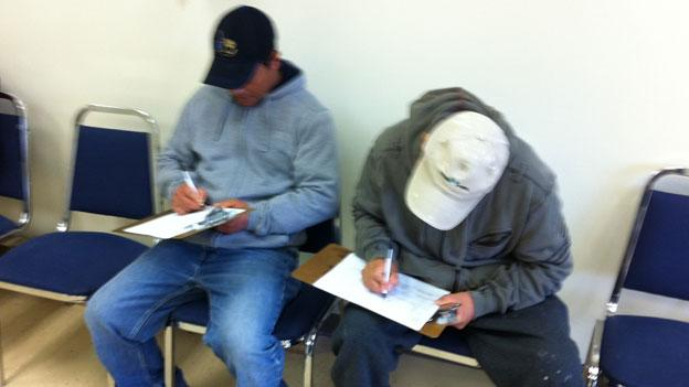 Eddie Segura and Jacinto Fox fill out paperwork at the new Centreville Labor Resource Center.