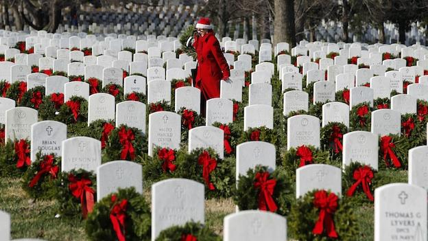 Volunteer Pati Redmond of Frederick, Md., helps to lay holiday wreaths over the graves of fallen soldiers at Arlington National Cemetery in Washington.