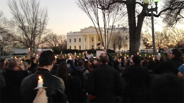 Hundreds converged on the White House Friday to hold a vigil for the estimated 26 dead.