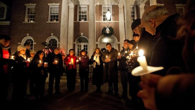 Mourners gather for a candlelight vigil outside the Edmond Town Hall, Saturday, Dec. 15, 2012, in Newtown, Conn. A gunman walked into Sandy Hook Elementary School in Newtown Friday and opened fire, killing 26 people, including 20 children.