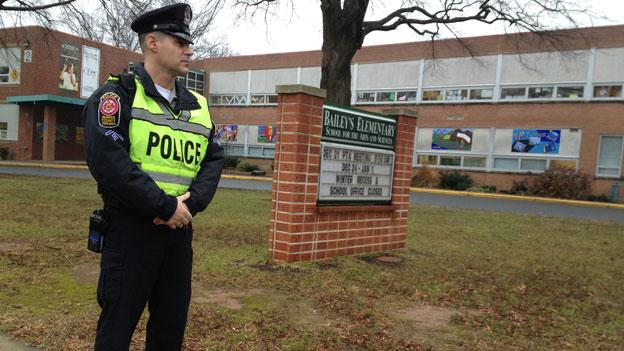 A police officer stands watch outside Bailey's Elementary School in Fairfax County.