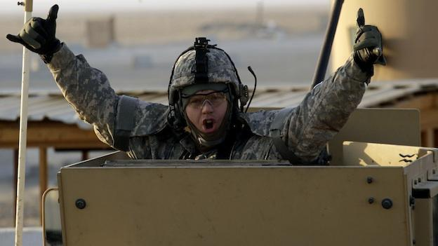 A soldier gestures from the gun turret of the last vehicle in a convoy of the US Army's 3rd Brigade, 1st Cavalry Division crosses the border from Iraq into Kuwait, Sunday, Dec. 18, 2011. The brigade's special troops battalion are the last American soldiers to leave Iraq.