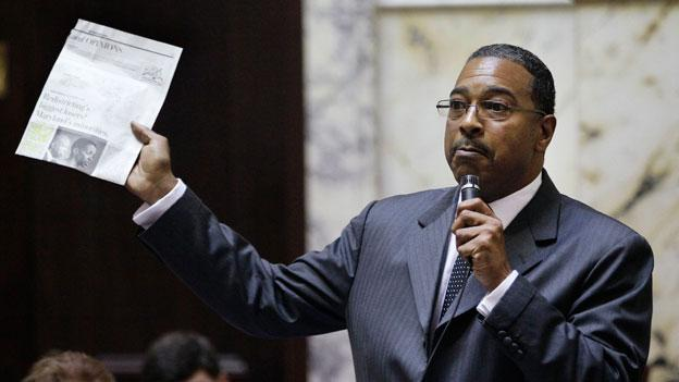 Maryland State Sen. C. Anthony Muse (D) holds up an editorial from The Washington Post asserting that minorities would suffer most if a proposed congressional redistricting plan passed. Nine black voters have sued the state over the plan, and a hearing on the suit begins today.