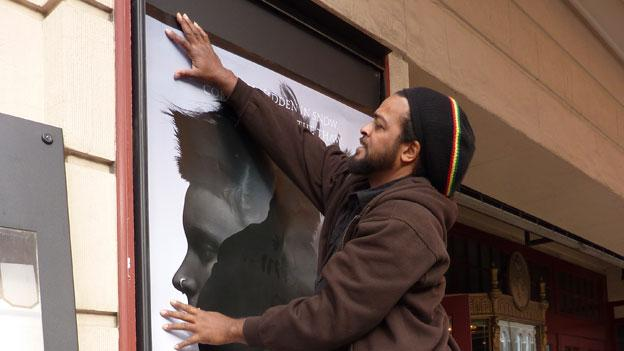 DNesstah Fields, Lincoln Theater's stage manager, puts up a poster promoting the four-week run of The Girl With the Dragon Tattoo on the front of the theater.
