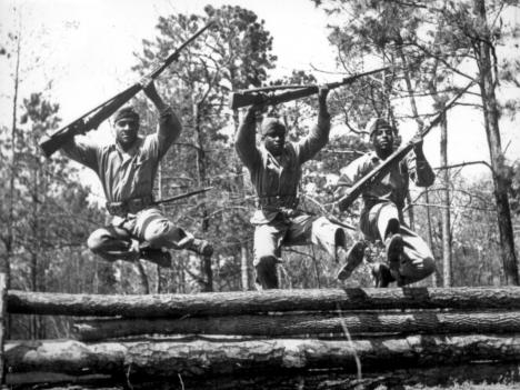 A trio of recruits in training to take their places as fighting Leathernecks in the U.S. Marine Corps, run the rugged obstacle course at Camp Lejeune, NC, Montford Point Camp. April 1943.