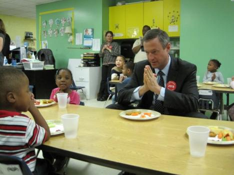 Governor Martin O'Malley saying grace with children before eating.