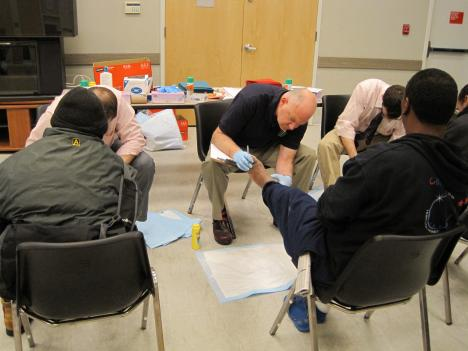 Dr. Cooper (center) and his staff examine feet at a homeless shelter in Rockville, Md. The doctors saw more than 200 people.