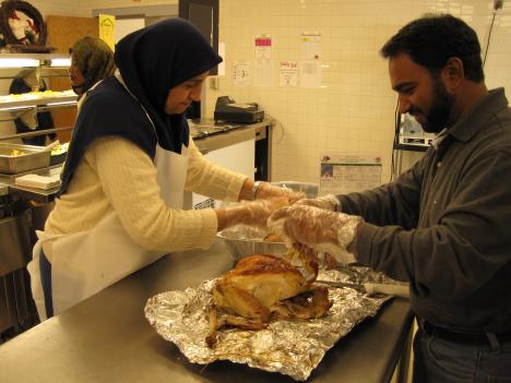 Farida Vaid and Ehsan Baig prepare food at Hutchinson Elementary School in Herndon. Baig, who moved to the U.S. from Pakistan, said this was the first time he had ever prepared a turkey.