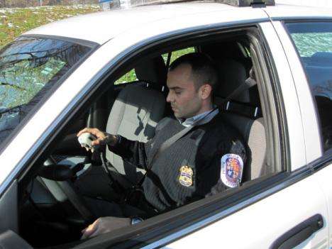 Corporal Nicholas Zook of the Prince George's County police deparTment waits in his cruiser outside the dispatch center to receive the inaugural 'test,' which was conducted for the benefit of the media in attendance.