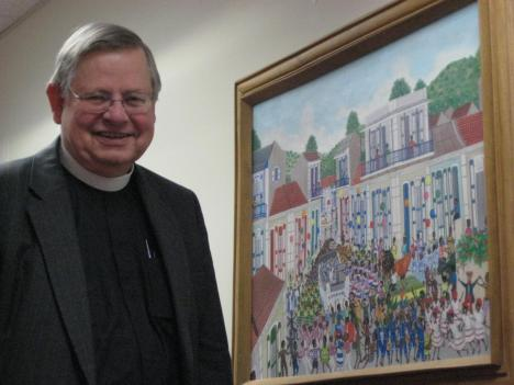 Father John Lawrence shows off one of many Haitian paintings at St. Patrick's.