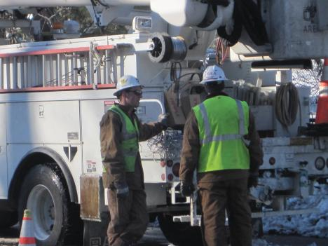 Pepco servicemen work to restore power.