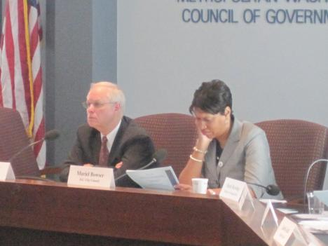 Falls Church City Councilman David Snyder (left) and D.C. Councilwoman Muriel Bowser (right) listen to a report on average daily trips taken at a Metropolitan Washington Council of Governments meeting.