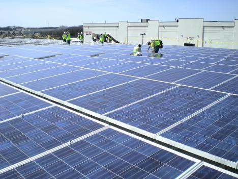 Workers install solar panels at the Rockville Ice Arena. Project managers with Standard Solar, Inc. say the 2,600 panels will be the largest roof-mounted solar system in the state.