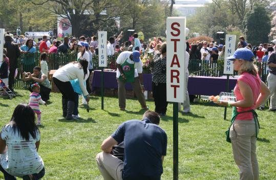 Parents encourage their children in the signature egg roll race on the South Lawn of the White House.