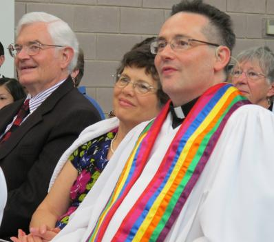 The Metropolitan Community Church formally installed Rev. Dwayne Johnson, in the rainbow stole, as senior pastor Sunday. His parents, both ministers in the Church of the Nazarene, joined the festivities.