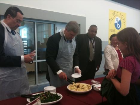 Vincent Gray, Chairman of the D.C. Council and Secretary of Agriculture Tom Vilsack serve children food at Alice Deal Middle School in Northwest D.C.