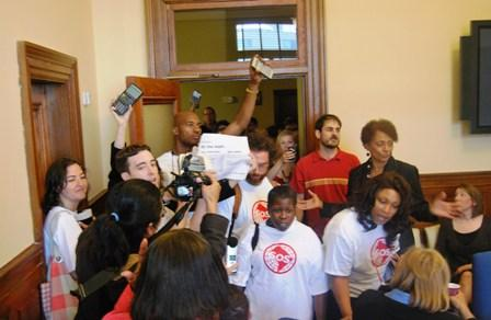 Activists interrupt a D.C. Council breakfast Wednesday morning to protest cuts to city social safety net services.