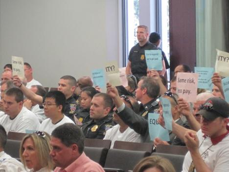 Police officers hold up signs protesting furloughs as county council members adopted the budget.