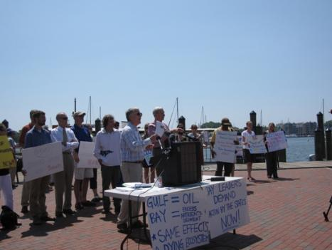 Former Maryland State Senator Gerald Winegrad talks about the recommendations to restore the Bay as other supporters hold signs on the city dock in Annapolis.