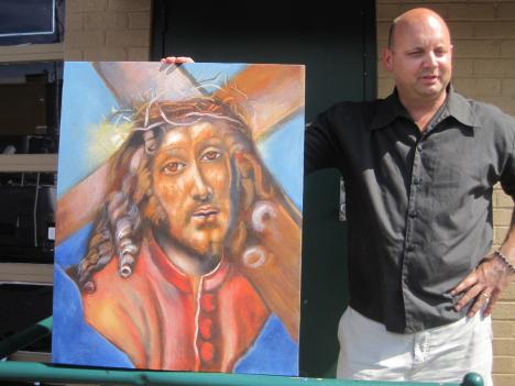 Tony Kurts displays a painting from his gallery created by murdered artist Azin Naimi.