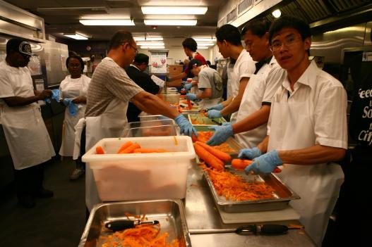 D.C. Central Kitchen staff and volunteers peel carrots in assembly lines, which allows them to quickly generate hundreds of meals every day.