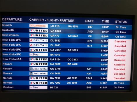 A flight information screen at Dulles International Airport shows cancelled flights in the region.