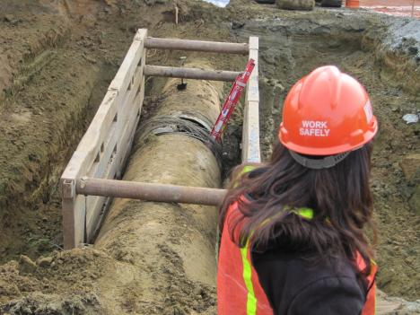 A WSSC worker examines the break in the 54-inch water main which is nearly 50-years old.