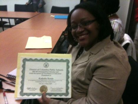 DCPS fired teacher Kadesha Bonds holds up her outstanding first year teacher award.