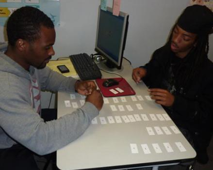 Two adult-literacy students sort through syllable flashcards at the Washington Literacy Council.
