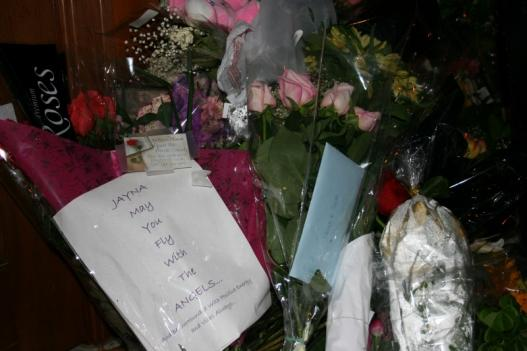 Flowers line the storefront of Lululemon Friday night. A vigil was held for Jayna Murray at the nearby Mindfulness Center.