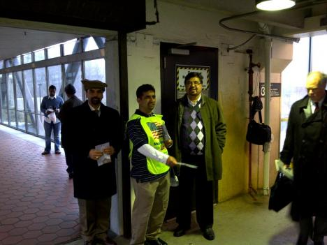 "A member of the Ahmadiyya Muslim Community passes out fliers as part of the ""Muslims for Loyalty"" campaign."