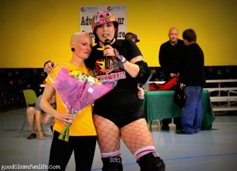 Salisbury Rollergirls founder Eva Paxton, aka Buster Skull (left), receives flowers from a teammate after the first official bout last week.