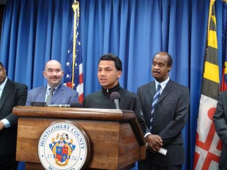 Ivan Echeverry speaks at the launch of a report on Latino youth. County Council Member George Leventhal (left) and County Executive Ike Leggett (right) announce how they will address the challenges presented in the report Monday.