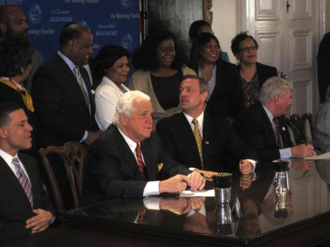 Maryland Gov. Martin O'Malley (front, third from left) speaks with Prince George's County Executive Rushern Baker (back row) before he signs an ethics reform law for the county in April. Baker is working to implement ethics reforms through his own task force.