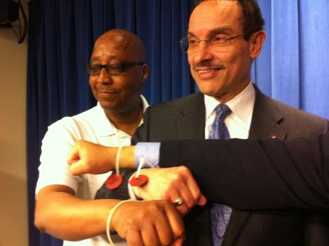D.C. Mayor Vincent Gray and activist Robert Brannum show off police wristbands from Monday's arrests.