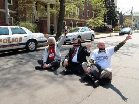 Shadow Sen. Mike Brown (center) and two other D.C. residents sit on Second Street. They were later arrested for civil disobedience at an April 15 protest against Congress's budget deal infringing on the District's rights.