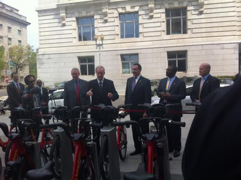City officials present the new Capital Bikeshare docking station at the Wilson Building.