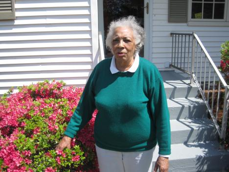Arminta Wood standing outside her spruced up house and yard in Alexandria, Va.