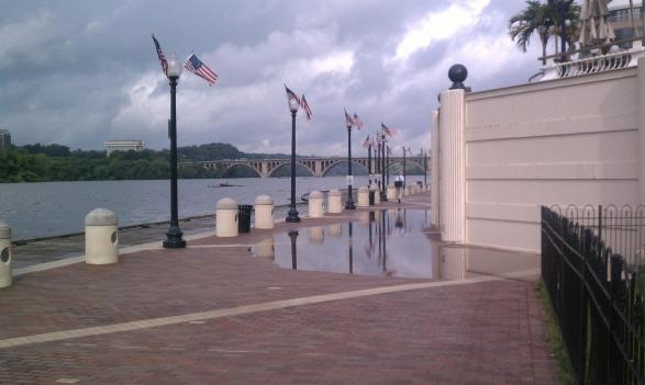 Waters from the Potomac River had already begun washing up on the shores in front of the Washington Harbour complex early this morning. The flood gates that can prevent the kind of flooding that plagued the area last month, are erected on the right.