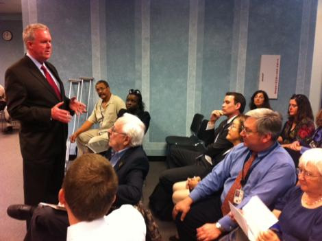 Council member Tommy Wells speaks to frustrated residents at a council hearing on redistricting Thursday.