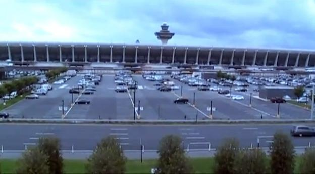 The disagreement over the Dulles Airport Metro station centers over whether it will be above ground (in the area of grass and trees in the foreground of the picture above) or underneath the parking lot.