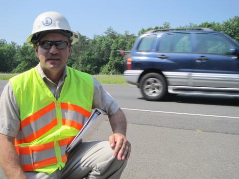 VDOT's Robert Wilson poses with a stretch of the new pavement blend on the Prince William County Parkway near Manassas.