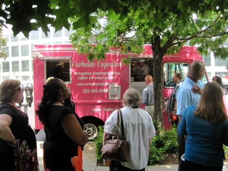 Food trucks, including Kristi Whitfield's Curbside Cupcakes, gather near the L'Enfant Metro Station around lunch time.