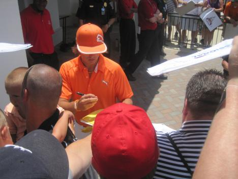 Fans crowd to get Rickie Fowler's autograph.