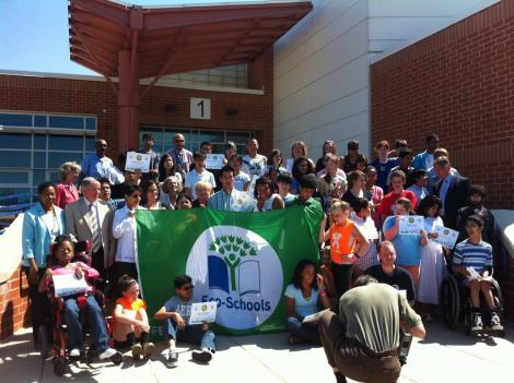 Students and staff at Lanier Middle School show off their green flag award for sustainability.
