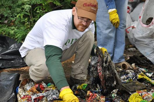 A DDOE staffer picks through trash during the All Hands partnership with Groundwork Anacostia on June 3.