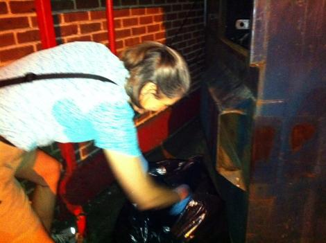 A Sierra Club volunteer peeks into trash bags for identifying information that would indicate who's recycling and who's not.