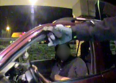 Surveillance photo of hooded thief robbing man at a drive-through ATM with a Taser.