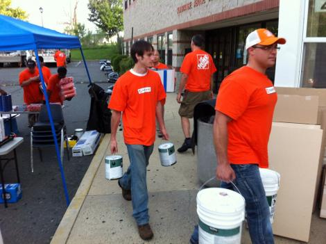 Volunteers from Home Depot load supplies into the Alexandria Community Shelter, which is getting a rapid fire face lift today.
